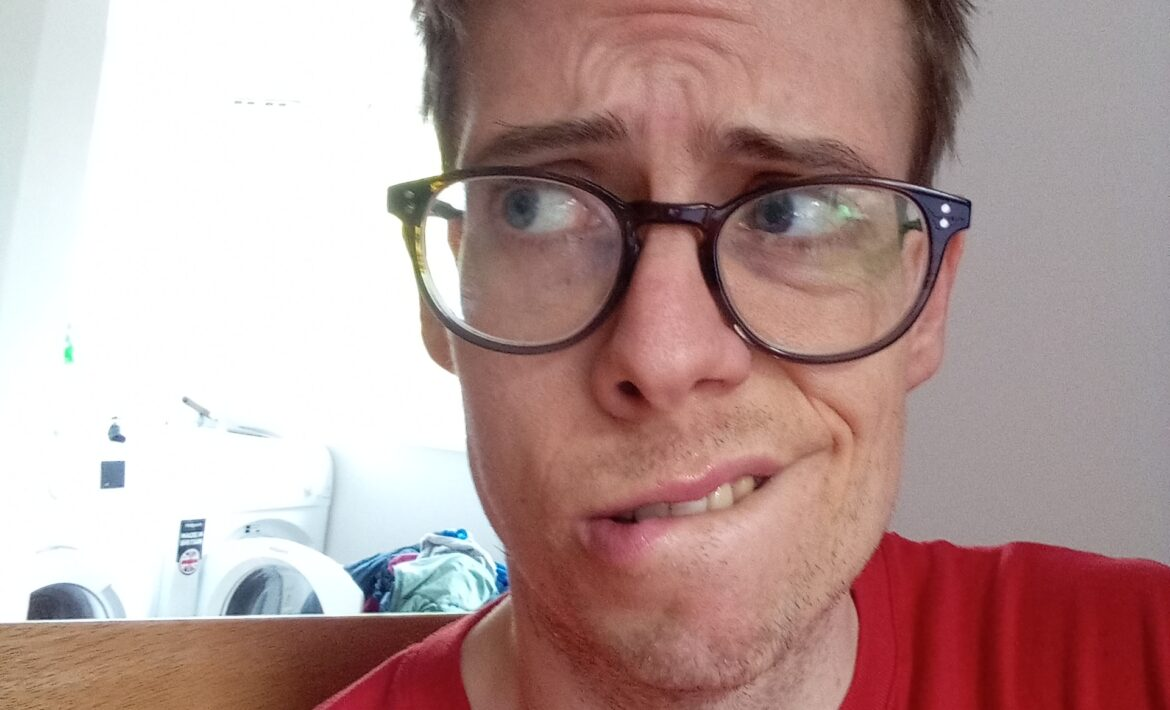 A picture of Jorik, a bespectacled autistic gay man in his thirties who hasn't had a shave for a few days. He has short, dark blond hair and is wearing a red Outdoorlads t-shirt. His face looks worried, biting his lip.